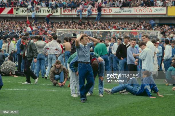 Fans on the pitch at Hillsborough football stadium in Sheffield after a human crush at an FA Cup semifinal game between Liverpool and Nottingham...