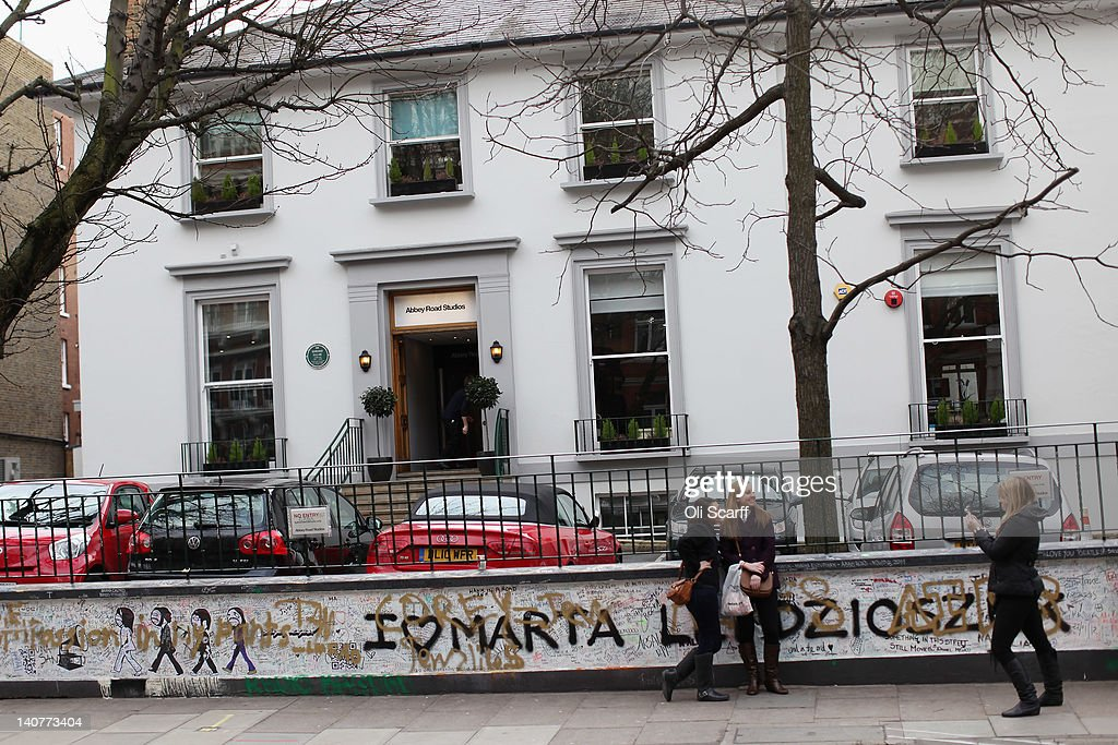 Fans outside Abbey Road Studios in St John's Wood on March 5, 2012 in London, England. Abbey Road in North London has been made famous by 1960s bands such as The Beatles and Pink Floyd who recorded in Abbey Road Studios. In particular, the cover of The Beatles' 1969 album 'Abbey Road' features the band on the pedestrian zebra crossing outside the studio. The crossing has become a popular destination for Beatles fans from around the world.