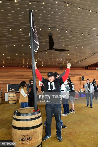 Fans participate in raising the Oakheart Rum flag during the Oakheart Genuine Spiced Rum Event at XFINITY Live Philadelphia on October 23 2016 in...