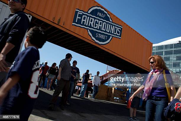 Fans pass by the entrance to the Fairgrounds a part of the shipping container project along Half St where food trucks and bands entertain the public...