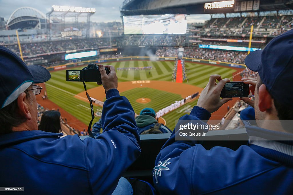 Fans photograph on field ceremonies prior to the game between the Seattle Mariners and the Houston Astros on Opening Day at Safeco Field on April 8, 2013 in Seattle, Washington.