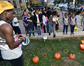 Fans play a ring toss with pumpkins at THE PEANUTS MOVIE Fall Festival Celebrating Charles M Schulz Day at Landmark Plaza on October 20 2015 in St...
