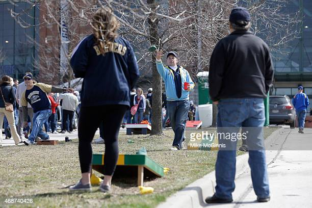 Fans play cornhole as they tailgate in the parking lot before the start of Opening Day between the Colorado Rockies and the Milwaukee Brewers on...