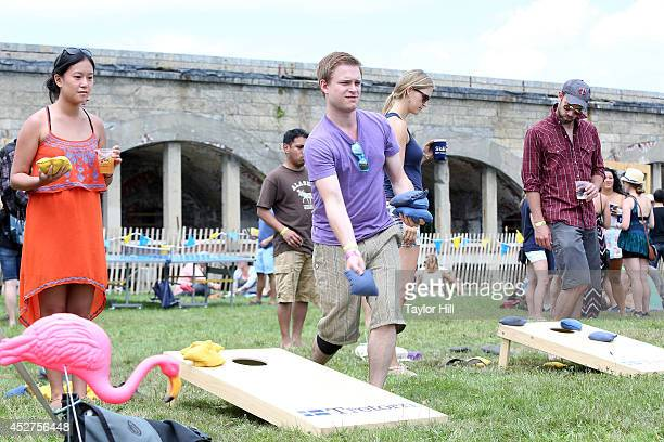 Fans play cornhole during the 2014 Newport Folk Festival at Fort Adams State Park on July 26 2014 in Newport Rhode Island