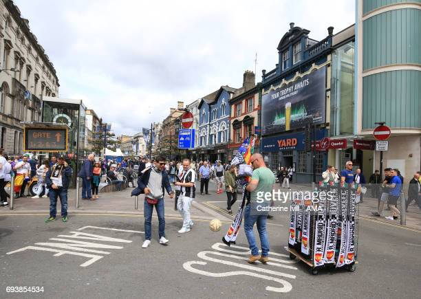 Fans play football next to a scarf seller in Cardiff city centre ahead of the UEFA Champions League Final match between Juventus and Real Madrid at...