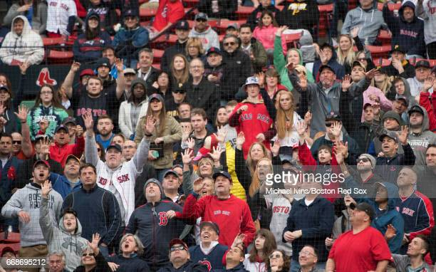 Fans plead for a baseball during a game between the Boston Red Sox and the Pittsburgh Pirates at Fenway Park on April 13 2017 in Boston Massachusetts