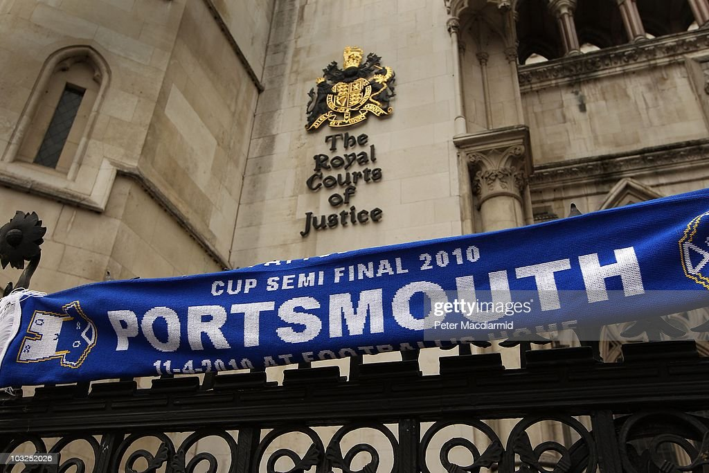 A fan's Portsmouth Football Club scarf hangs on the fence outside The High Court on August 5 2010 in London England The football club has won it's...