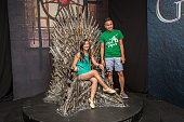 Fans pose for a photo on the Iron Throne from the HBO hit series 'Game of Thrones' at ComicCon International Day 3 on July 22 2016 in San Diego...