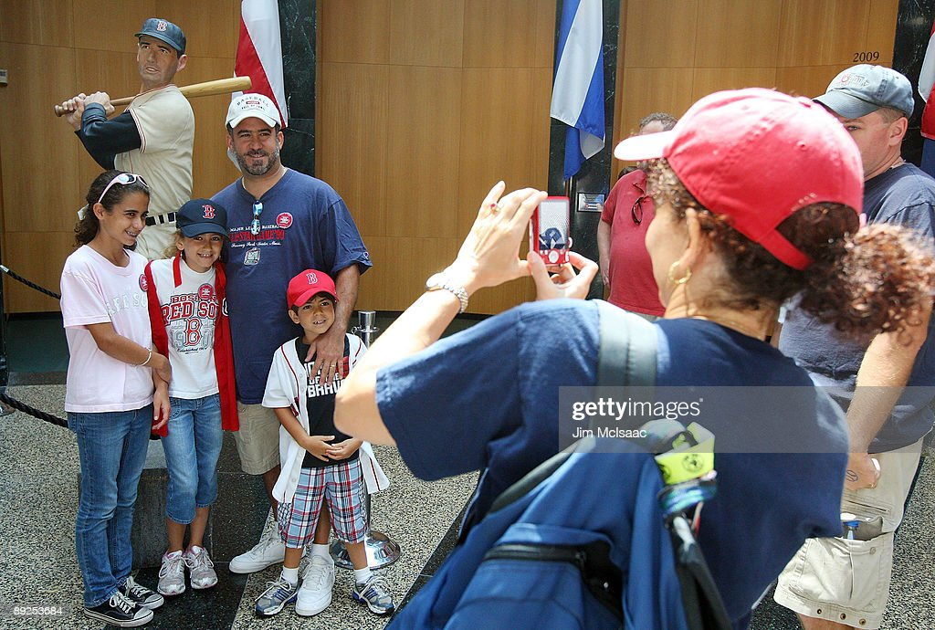 Fans pose for a photograph at the National Baseball Hall of Fame during induction weekend on July 25 2009 in Cooperstown New York