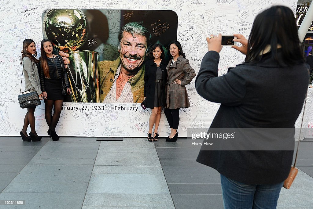Fans pose for a picture in front of the display of Dr. Jerry Buss after his memorial service outside the Nokia Theatre L.A. Live on February 21, 2013 in Los Angeles, California.