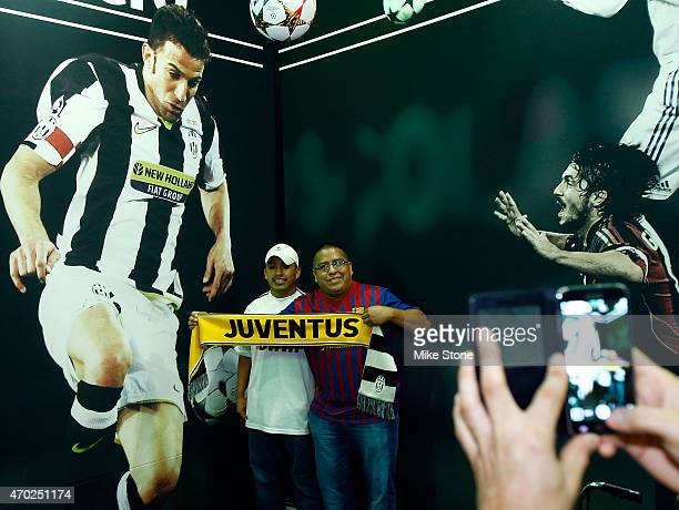 Fans pose in front of one of the wall murals at the 2015 UEFA Champions League Trophy Tour presented by Heineken exhibit on April 18 2015 in Dallas...