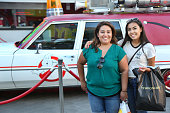 Fans pose in front of the 'Ghostbusters' Cadillac Fleetwood Station Wagon at AMC Universal City Walk on July 14 2016 in Universal City California