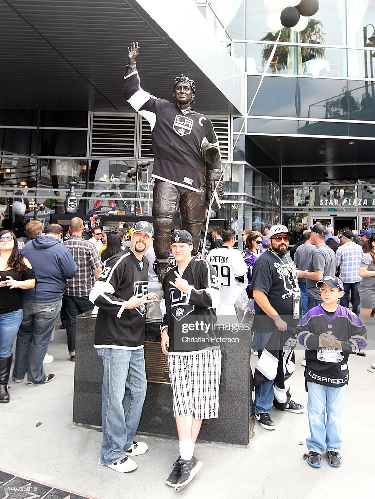 Fans pose in front of the Wayne Gretzky statue as it is dressed in a Los Angeles Kings jersey outside Staples Center before the Kings take on the New Jersey Devils in Game Three of the 2012 Stanley Cup Final on June 4, 2012 in Los Angeles, California.