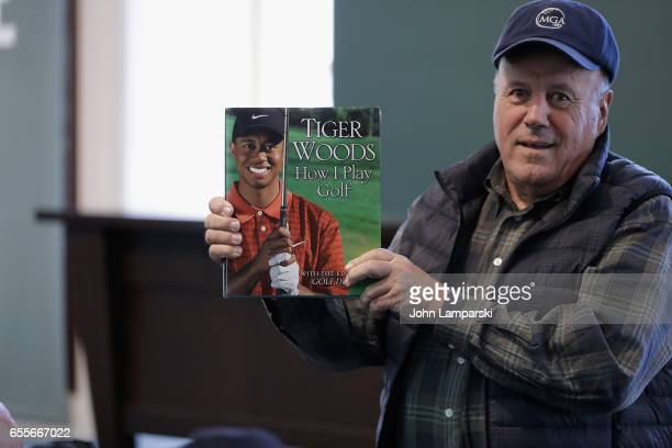 Fans pose with a book as professional golf player Tiger Woods signs copies of his new book 'The 1997 Masters My Story' at Barnes Noble Union Square...