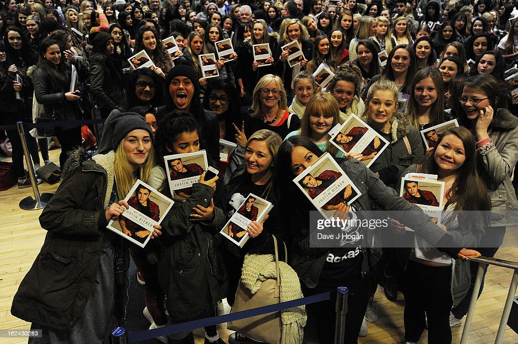Fans pose with a copy of <a gi-track='captionPersonalityLinkClicked' href=/galleries/search?phrase=Justin+Bieber&family=editorial&specificpeople=5780923 ng-click='$event.stopPropagation()'>Justin Bieber</a>'s new book during his 'Just Getting Started' book launch at the Congress Centre on February 23, 2013 in London, United Kingdom.