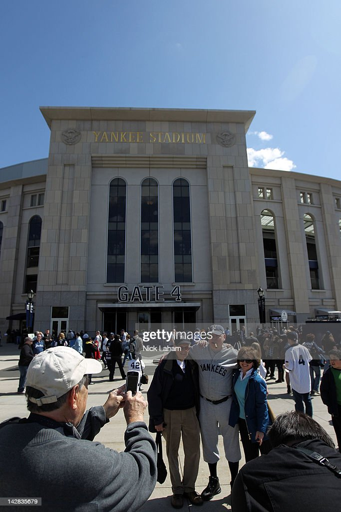 Fans pose with a man dressed as Babe Ruth in front of Yankee Stadium prior to the home opener between the New York Yankees and the Los Angeles Angels on April 13, 2012 in the Bronx borough of New York City.