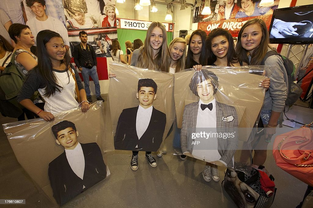 Fans pose with cardboard versions of Zayn Malik and Harry Styles during the opening of a temporary store selling merchandising of British-Irish boy band One Direction on August 16, 2013, at the Waasland Shopping Center in Sint-Niklaas. The shopping center issued extra security to receive the band's fans.