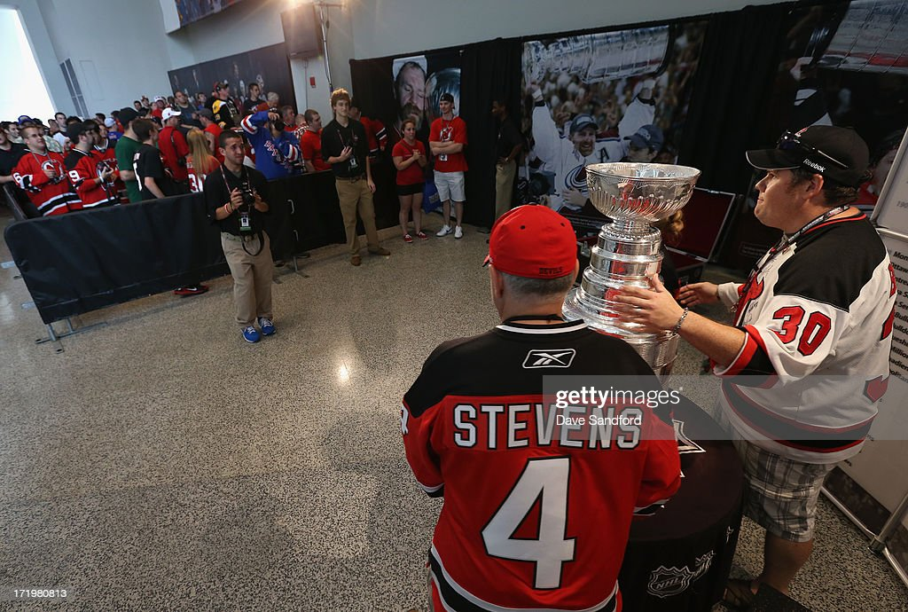 Fans pose with the Stanley Cup during the 2013 NHL Draft - Fan Fest and Memorabilia Show at Prudential Center on June 30, 2013 in Newark, New Jersey.