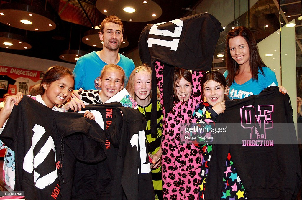Fans pose with their merchandise and staff from a The Edge radio station after winning a competition inside the official One Direction merchandise store on April 20, 2012 in Wellington, New Zealand. The 1D fan store will sell official merchandise for four days only, closing on Monday, April 20. One Direction is on tour in New Zealand performing a show in Auckland and Wellington before returning to the UK.