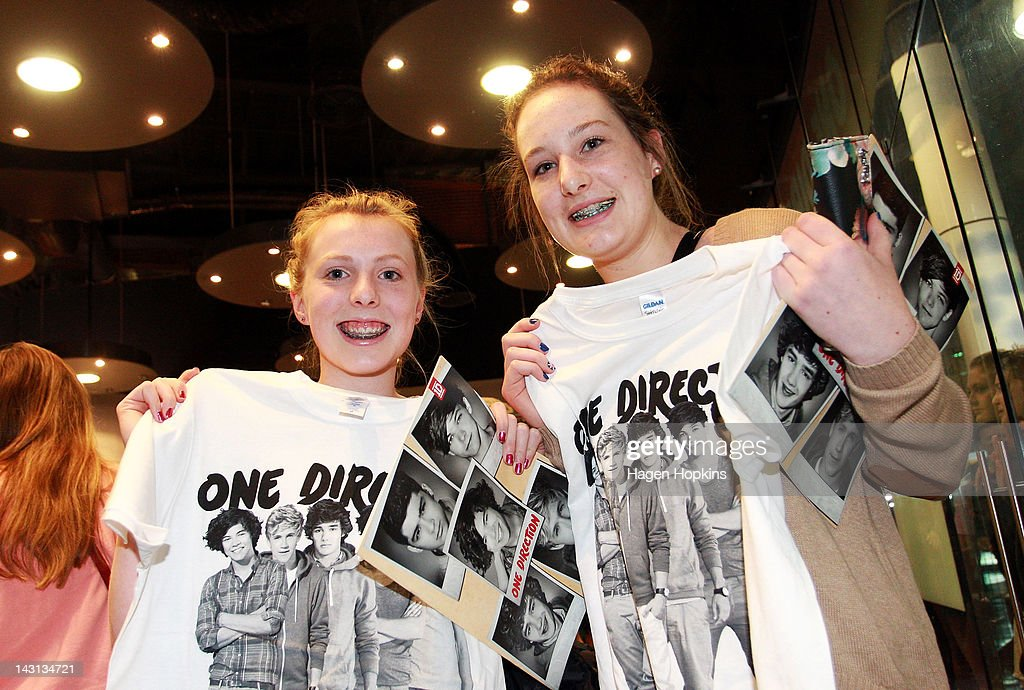 Fans pose with their merchandise inside the official One Direction merchandise store on April 20, 2012 in Wellington, New Zealand. The 1D fan store will sell official merchandise for four days only, closing on Monday, April 20. One Direction is on tour in New Zealand performing a show in Auckland and Wellington before returning to the UK.