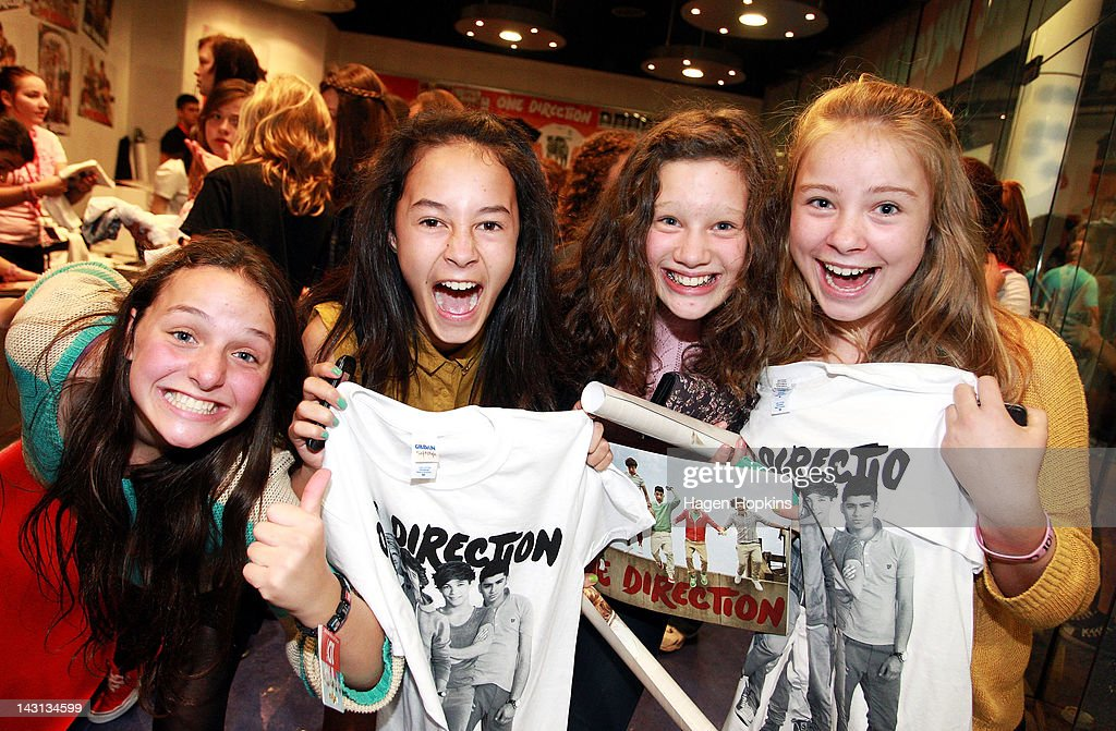 Fans pose with their merchandise outside the official One Direction merchandise store on April 20, 2012 in Wellington, New Zealand. The 1D fan store will sell official merchandise for four days only, closing on Monday, April 20. One Direction is on tour in New Zealand performing a show in Auckland and Wellington before returning to the UK.