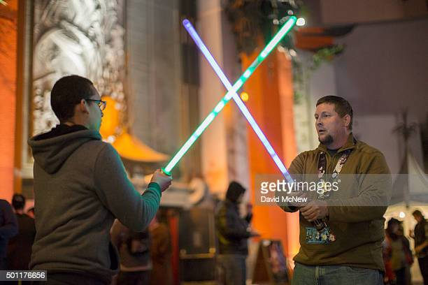 Fans practice light saber fighting technique as they camp out in the TLC Chinese Theatre courtyard for the premiere of Walt Disney Pictures And...