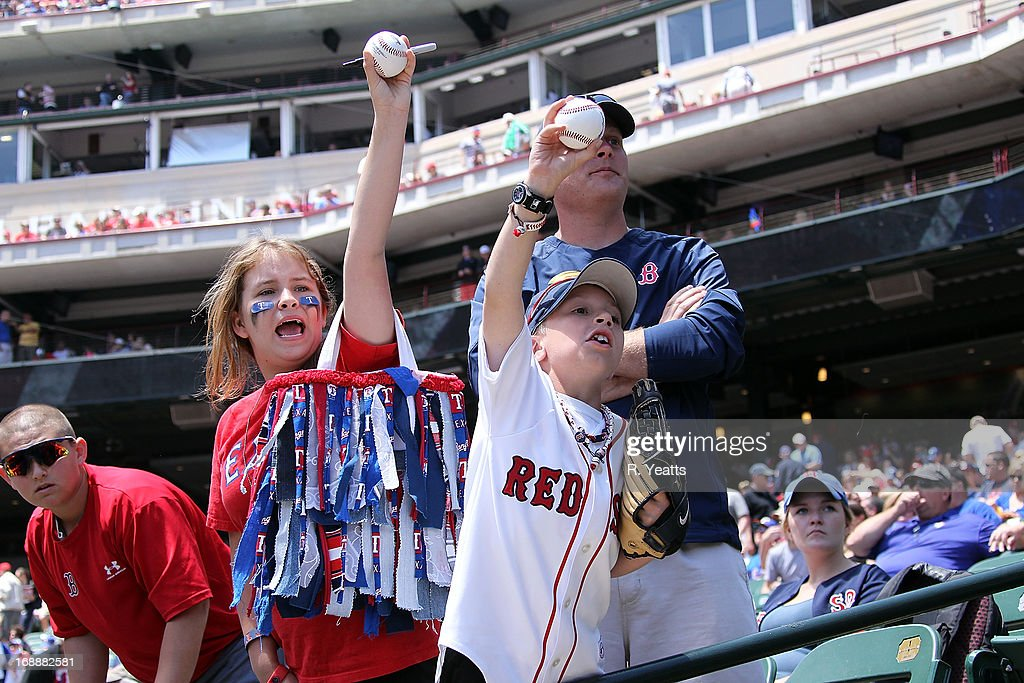 Fans prior to the start of the game between the Boston Red Sox and the Texas Rangers seek autographs from the Red Sox dugout at Rangers Ballpark in Arlington on May 5, 2013 in Arlington, Texas.
