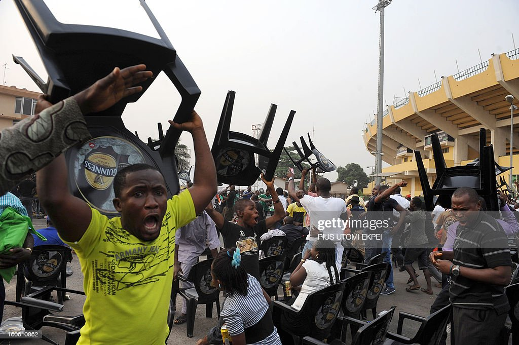 Fans raise chairs to celebrate Nigeria football team's victory over Ivory Coast to advance into the semi final of the 2013 African Cup of Nations on February 3, 2013 at a public viewing centre in Lagos. Supposed underdogs Nigeria downed favourites Ivory Coast 2-1 in an absorbing quarter-final to set up a last-four meeting with Mali.