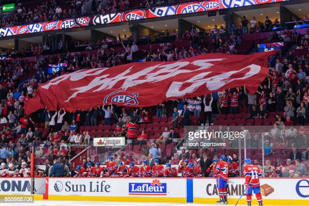 Fans raise the Go Habs Go banner before the start of the NHL preseason game between the New Jersey Devils and the Montreal Canadiens on September 21...