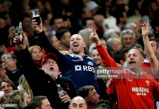 Fans raise their glasses to a section of the crowd as they sing the Flower of Scotland during the Six Nations international rugby union match between...