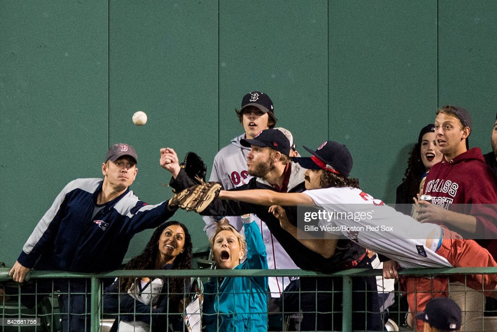 Fans reach for a ground rule double hit by Brock Holt #12 of the Boston Red Sox during the eighth inning of a game against the Toronto Blue Jays on September 4, 2017 at Fenway Park in Boston, Massachusetts.