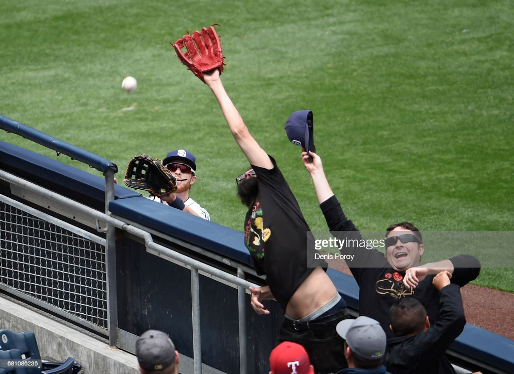 Fans reach out for a foul ball next to Cory Spangenberg #15 of the San Diego Padres during the fourth inning of a baseball game against the Texas Rangers at PETCO Park on May 9, 2017 in San Diego, California. No one was able to make the catch.