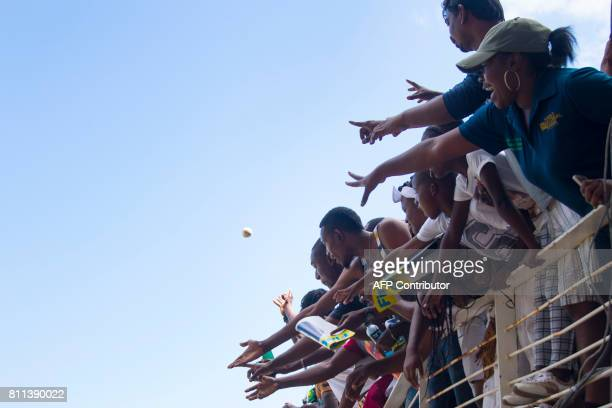 Fans reach out for a souvenir ball during the T20 match between West Indies and India at the Sabina Park Cricket Ground in Kingston Jamaica on July 9...