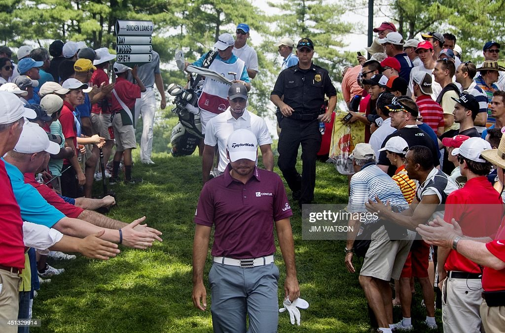 Fans reach out to shake hands with US golfers <a gi-track='captionPersonalityLinkClicked' href=/galleries/search?phrase=Tiger+Woods&family=editorial&specificpeople=157537 ng-click='$event.stopPropagation()'>Tiger Woods</a> (C- white shirt) and Australian golfer <a gi-track='captionPersonalityLinkClicked' href=/galleries/search?phrase=Jason+Day+-+Golfer&family=editorial&specificpeople=4534484 ng-click='$event.stopPropagation()'>Jason Day</a> (front) as they depart the green during the second round of the Quicken Loans National at Congressional Country Club in Bethesda, Maryland, June 27, 2014. AFP PHOTO / Jim WATSON