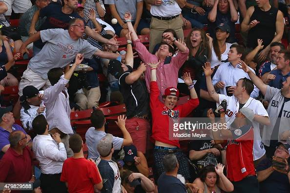 Fans reach to catch a foul ball during the first inning at Fenway Park on July 7 2015 in Boston Massachusetts