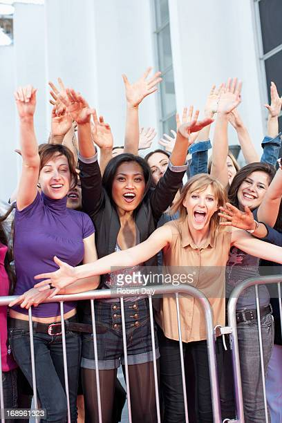 Fans reaching out from behind barrier