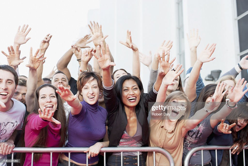 Fans reaching out over barrier : Stock Photo