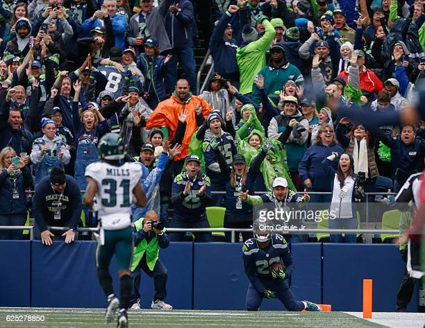 Fans react after running back CJ Prosise of the Seattle Seahawks scored a touchdown against the Philadelphia Eagles at CenturyLink Field on November...