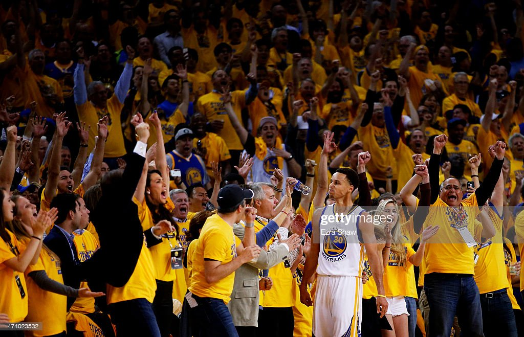 Fans react after Stephen Curry of the Golden State Warriors scored at the end of the seocnd quarter against the Houston Rockets during Game One of...
