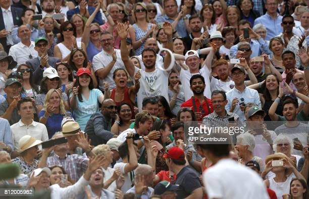 Fans react as Switzerland's Roger Federer throws his headband and wristband toards them after winning against Bulgaria's Grigor Dimitrov during their...
