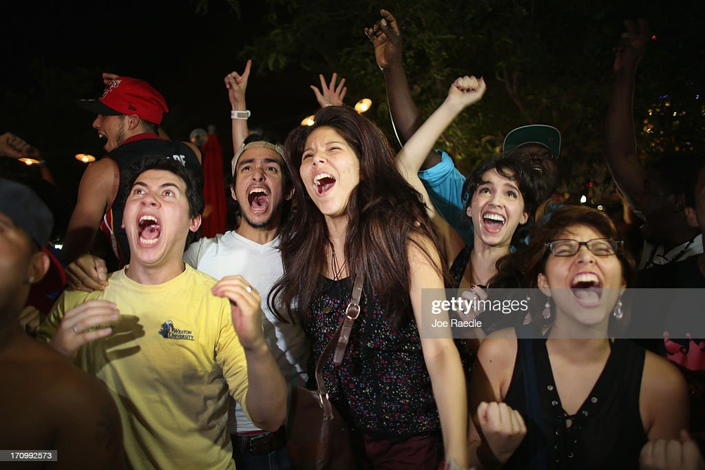 Fans react as they watch on television the Miami Heat win the NBA title against the San Antonio Spurs June 20, 2013 in Miami, Florida. The Heat won back to back championships.