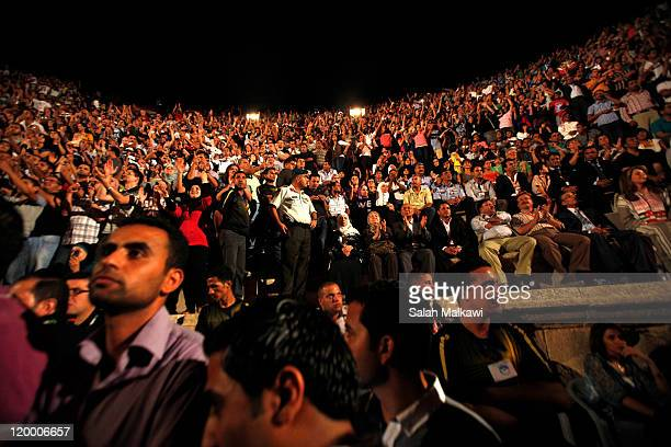 Fans react to Lebanese singer Najwa Karam performing at the southern amphitheatre during the Jerash Festival on July 28 2011 in Jerash Jordan The...