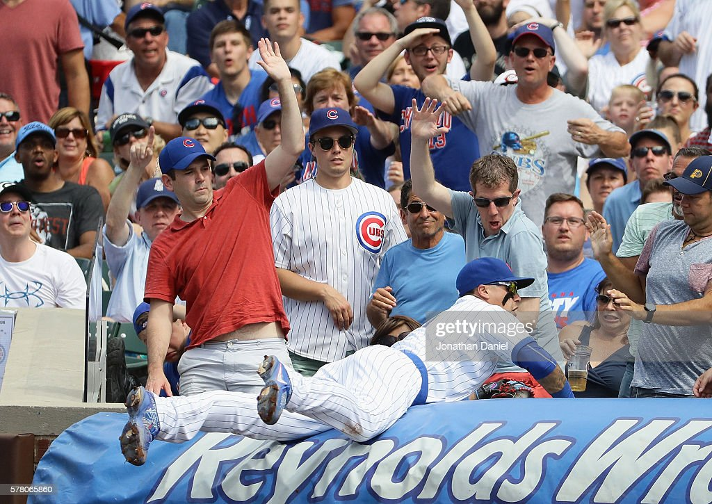 Fans reacts as Javier Baez #9 of the Chicago Cubs dives over the tarp to make a catch in the 7th inning against the New York Mets at Wrigley Field on July 20, 2016 in Chicago, Illinois. The Cubs defeated the Mets 6-2.