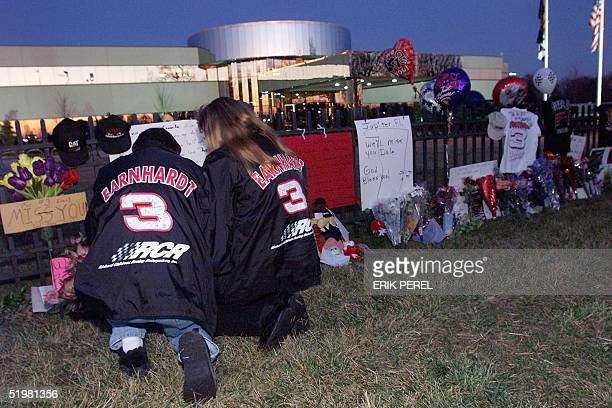 NASCAR fans Ronnie and Vickie Pethel of Concord NC say a prayer at a memorial outside driver Dale Earnhardt's corporate headquarters 19 February 2001...