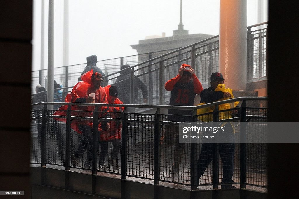 Fans run down the ramps to escape severe weather as the NFL football game between the Chicago Bears and the Baltimore Ravens at Soldier Field in Chicago on Sunday, Nov. 17, 2013.