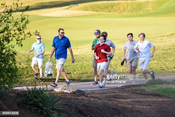 Fans run to keep up with the group of Sergio Garcia of Spain and Shane Lowry of Ireland on the 17th hole during round one of the World Golf...