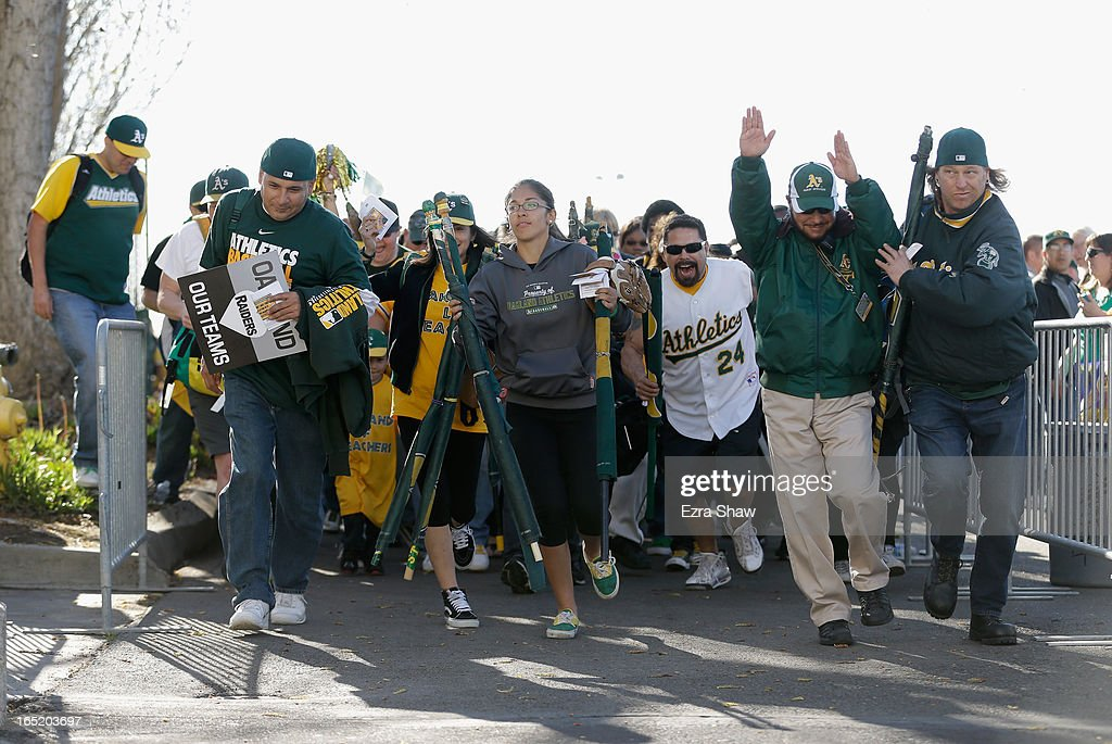 Fans run to the stadium after the gates are opened two hours before the start of the Oakland Athletics game against the Seattle Mariners on Opening Day at O.co Coliseum on April 1, 2013 in Oakland, California.