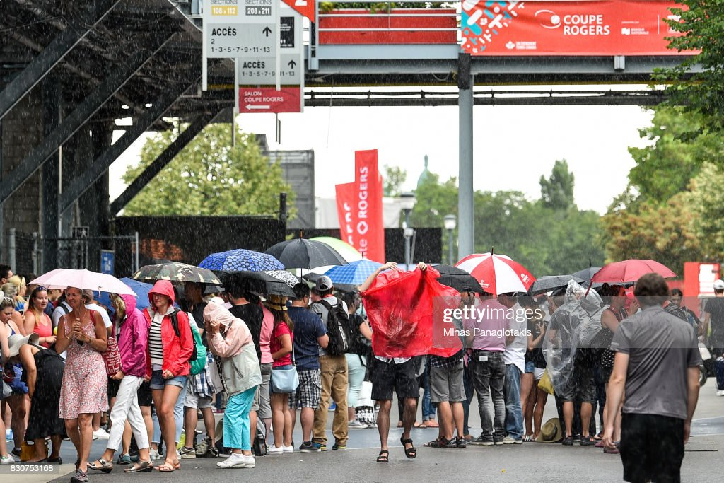 Fans rush for cover as it begins to rain on day nine of the Rogers Cup presented by National Bank at Uniprix Stadium on August 12, 2017 in Montreal, Quebec, Canada.