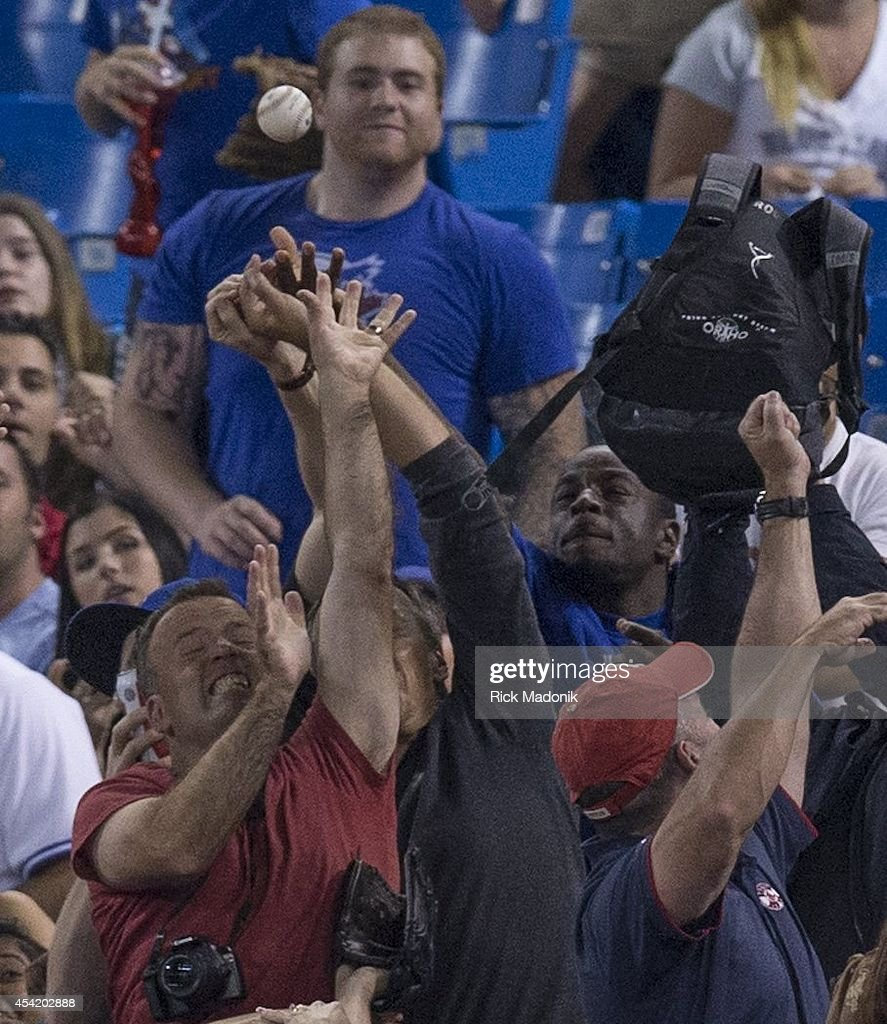 TORONTO - AUGUST 25 - Fans scramble for a fly ball in the stands. Toronto Blue Jays Vs Boston Red Sox during MLB action at Rogers Centre on August 25, 2014.
