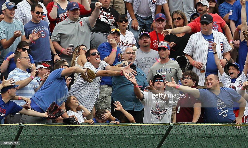 Fans scramble for a home run ball hit by Dexter Fowler of the Chicago Cubs against the Philadelphia Phillies in the 1st inning at Wrigley Field on May 28, 2016 in Chicago, Illinois.